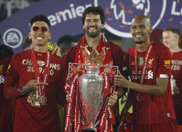 Trio brasileiro comemora o título da Premier League.